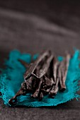 Several vanilla pods on a piece of turquoise cloth
