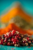 Mixed peppercorns in front of assorted spices