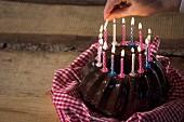 Kerzen auf einem Schokoladen-Guglhupf anzünden
