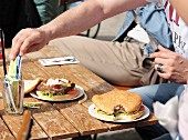 Burgers on a table in a beer garden in the sunshine; a man's hand reaching for a sachet of mayonnaise