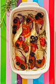 Baked fillet of fish with red onions, tomatoes, black olives and rosemary