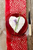 A heart-shaped Neufchatel cheese with a sprig of lavender on a red and white silk cloth
