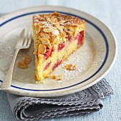 A slice of raspberry cake with flaked almonds