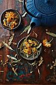 Getrocknete Ringelblumen, Lindenblüten und eine gusseiserne Teekanne