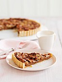 A piece of pecan pie in front of sliced pecan pie