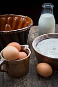 Baking ingredients: milk in a glass bottle, eggs and flour in clay bowls and an old bundt cake pan