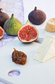 Fresh figs, fig pulp, camembert, a knife and a slice of baguette