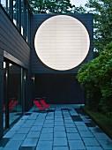 Anbau eines Wohnhauses mit grosser, weisser Kreisfläche auf dunkler Fassade in Abenddämmerung; auf Terrasse Liegestühle mit rotem Bezug