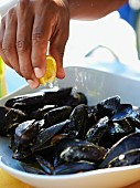 Hand Squeezing a Lemon Over Fresh Mussels