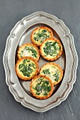 Spinach tartlets on a silver tray (view from above)