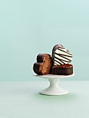 Three chocolate petit fours on a cake stand