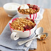 Boysenberry-apple crumbles with cream, with a bite taken out of one