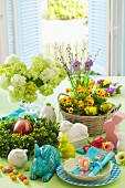 Table set for Easter with spring flowers, china rabbits and Easter place setting