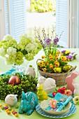Gedeckter Ostertisch mit Frühlingsblumen, Porzellanhasen und Ostergedeck