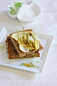 Wholegrain bread with butter and bulbs of wild garlic
