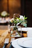 Kleiner Blumenstrauss auf einer rustikalen Hochzeitstafel im Frühling