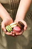 Hands holding four macarons