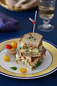 A Stacked Sandwich with Salmon, Avocado, Eggs and Yellow Tomatoes