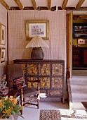 The corner of a room in an English country house with an Asian chest of drawers, a lamp and a leather chair