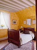 A guest bedroom in an English country house with a wooden bed and yellow walls