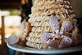 A tower of coconut biscuits with floral decoration for a celebration