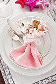 Spring table setting with pink napkin and white flowers