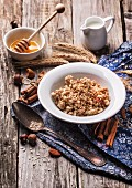 Plate of muesli with milk, honey, cinnamon and nuts over old wooden background