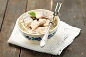 Chunks of pickled herring in a bowl