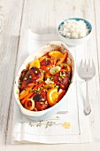 Oven-roasted chicken leg with carrots and oranges