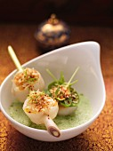 Coconut and spinach soup with fried scallops on a lemongrass skewer