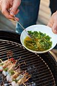 Prawn skewer being drizzled with herb & garlic marinade