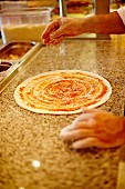 Pizza base being sprinkled with cheese