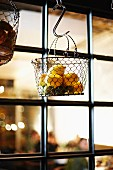 Lemons hanging in a wire basket in a restaurant