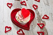 A pink cupcake with red hearts