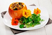 Fried Chantarelles in a Pumpkin wilth Wild Herbs Salad, selective focus