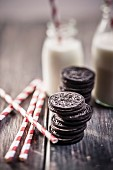 Stacks of Oreo cookies with milk bottles and drinking straws on a wooden slab