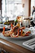 Riesengarnelen mit Gemüse und Wein auf Restauranttisch
