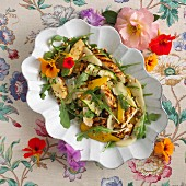 Summery chicken salad with peppers, rocket and nasturtium flowers