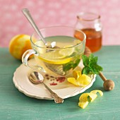Ginger and lemon tea in a glass teacup