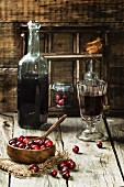 Wooden bowl of cranberries with bottle and glass of berry wine