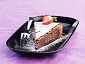 A slice of chocolate torte with icing sugar and a strawberry
