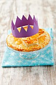 Galette des Rois (king cake) with a paper crown