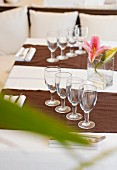 Glasses, napkins, cutlery and lilies on a restaurant table