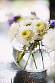 Fresh cut flowers in a spherical vase on a table