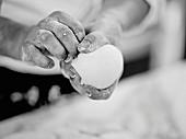 Hands holding a ball of dough