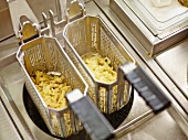 Containers of boiled pasta in a commercial kitchen