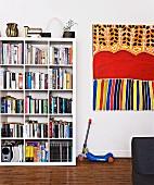 Weisses Bücherregal mit quadratischen Einteilungen, daneben Kinderroller und modernes, buntes Bild an Wand (Kunst der Aborigines)