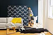 Sitzbereich mit Sofa, Tierfellteppich & Couchtisch abgetrennt durch Raumteilerregal tapeziert mit schwarz-weißem, floralen Muster auf der Rückwand