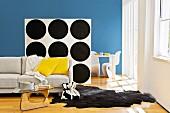 Sitzbereich mit Sofa, Tierfellteppich & Couchtisch abgetrennt durch Raumteilerregal tapeziert mit schwarz-weißem, Punktmuster auf der Rückwand