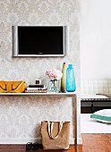 Wandbildschirm an weißer Brokat-Tapete mit schlichtem Ablagen-Konsolentisch, verschiedenen Vasen und senfgelber Handtasche